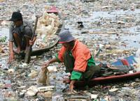 Uomini indonesiani raccolgono rifiuti sul fiume Citarum per il riciclaggio
